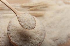 Nära övre sikt av jasminris i en träbunke, sked och öra av ris på träbakgrund royaltyfri foto