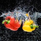 nära övre sikt av röda och gula spanska peppar i vatten arkivfoto