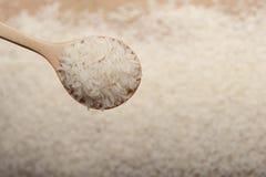 Nära övre sikt av ris i en träsked på träbakgrund arkivfoto