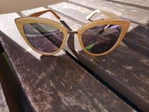 Nära övre sikt av solglasögon som sitter på en tabell arkivbilder