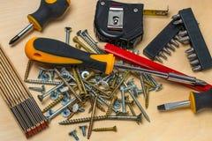 Nära övre sikt av vanliga hjälpmedel för faktotum/hobbyman Tumstock skruvmejslar, skruvar, blyertspenna arkivfoton