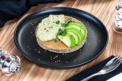 Nära övre sikt på bovetemjölpannkakan med guacamole från avacado som tjänas som på den mörka plattan på träbakgrund Sunt strikt v royaltyfria foton