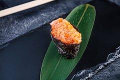 Nära övre sikt på den gunkan sushi med kryddig sås och laxen på mörk stenbakgrund Ny japansk kokkonst asiatisk mat Sushi royaltyfria bilder