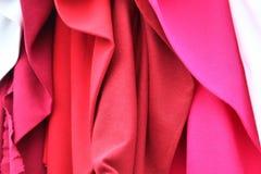 Nära övre sikt på färgrikt hänga och vikta tyger och textiler i hög upplösning som finnas på en tygmarknad i Flensburg royaltyfri foto