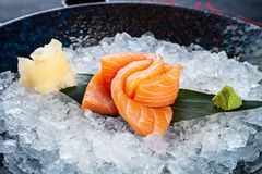 N?ra ?vre sikt p? sashimien fr?n laxen som tj?nas som p? is B?sta sikt p? traditionell japansk mat Ny tonfisk som ?r klar f?r, ?t royaltyfri bild