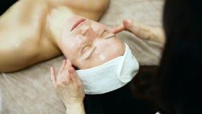 Nära övre skott av den ansikts- massagen för brunnsort Framsidamassage i sk?nhetbrunnsortsalong arkivfilmer
