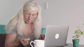 Nära övre skott av den pensionerade farmodern för gammal kvinna som hemma använder bärbara datorn i vardagsrummet Äldre kvinna so arkivfilmer