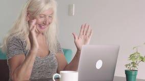 Nära övre skott av den pensionerade farmodern för gammal kvinna som hemma använder bärbara datorn i vardagsrummet Lycklig äldre a arkivfilmer