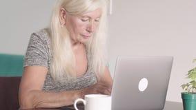 Nära övre skott av den pensionerade farmodern för gammal kvinna som hemma använder bärbara datorn i vardagsrummet Trött äldre aff lager videofilmer