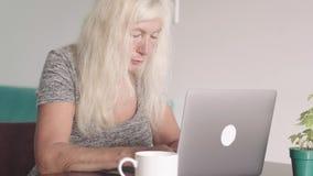 Nära övre skott av den pensionerade farmodern för gammal kvinna som hemma använder bärbara datorn i vardagsrummet Trött äldre aff stock video