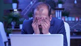 Nära övre skott av den trötta och utmattade affärsmannen som sent arbetar - natt stock video