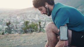Nära övre skott av en ung vit manlig löpare som binder hans skor och står se upp sikten för hans körning arkivfilmer