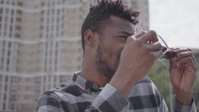 N?ra ?vre st?ende av afrikansk amerikanmananseendet mot bakgrunden av stads- byggnad som skelar i solen, d? stock video