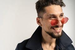 Nära övre stående av att le den stiliga mannen i solglasögon i svart omslag royaltyfri fotografi