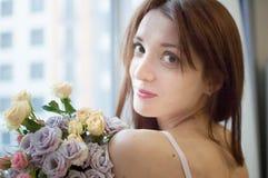 Nära övre stående av att le vuxet flickaanseende nära fönstret med en bukett av blommor och att se kameran arkivfoto