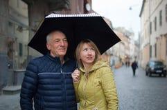 N?ra ?vre st?ende av den ?ldre mannen och hans unga blondin-haired frun som omfamnar sig och st?r under deras paraply royaltyfria foton