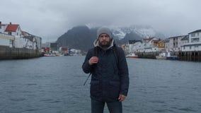 Nära övre stående av den allvarliga mannen av den Norge pir, bakgrundsfartyg stock video