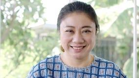 Nära övre stående av den asiatiska attraktiva kvinnan som ler säkert nätt för brunett stock video