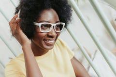 Nära övre stående av den attraktiva afrikanska damen som bär modernt vitt glasögon royaltyfri fotografi