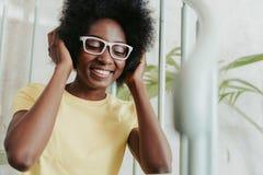 Nära övre stående av den attraktiva afrikanska damen som lyssnar till musik royaltyfri bild
