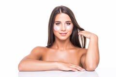 Nära övre stående av den attraktiva flickan med nakna skuldror använda och att ha som applicerar lappar under nära ögon, kamp med royaltyfri foto