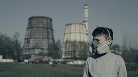 Nära övre stående av den bärande föroreningmaskeringen för ung pojke mot fabrikslampglas Luftf?roreningbegrepp Grabben vänder lager videofilmer