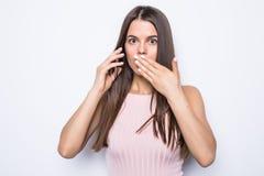Nära övre stående av den chockade kvinnan som talar till något på telefonen på vit bakgrund royaltyfri bild