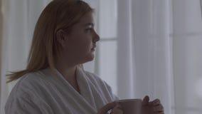 Nära övre stående av den fylliga flickan i det vita badrockanseendet nära stort golv-till-tak fönster med koppen kaffe eller te lager videofilmer