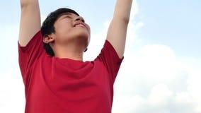 Nära övre stående av den gladlynta asiatiska pojken som ler lycklig skämtsam tyckande om dag lager videofilmer