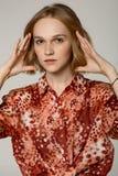 Nära övre stående av den härliga blonda flickan i röd skjorta med piercing i näsan royaltyfri foto