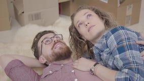 Nära övre stående av den skäggiga mannen i exponeringsglas och nätt kvinna med lockigt hår som tillsammans ligger på fluffig matt lager videofilmer