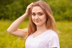 Nära övre stående av den unga härliga blonda kvinnan med starighthår som poserar i äng i solig sommar eller vårdagen som ser royaltyfri foto