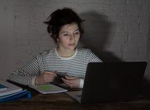 Nära övre stående av en överansträngd och trött ung kvinna som sent studerar på natten på lynnigt ljus arkivbilder