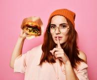Nära övre stående av en hungrig ung kvinna som äter hamburgaren över rosa bakgrund royaltyfria foton