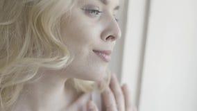 Nära övre stående av en le blond kvinna som utanför ser till och med fönster actinium H?rlig ung flicka med lockigt h?r arkivfilmer