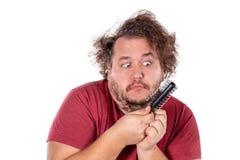 Nära övre stående av feta manförsök att kamma hans tilltrasslade och stygga hår med en liten svart hårkam som isoleras på vit bak arkivfoto
