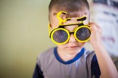 Nära övre stående av lite att le pojken i roliga exponeringsglas för en sol arkivfoton