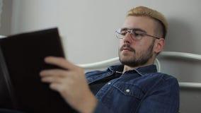 Nära övre stående av Satisfied den unga attraktiva mannen med exponeringsglas och gult hår som läser en bok, medan lägga i säng p arkivfilmer