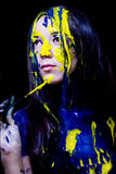 Nära övre stående för skönhet/för mode av kvinna målad blått och guling med borstar och målarfärg på svart bakgrund Royaltyfria Bilder
