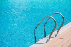Nära övre stege för hastigt greppstänger med blått vatten i simbassäng i bakgrunden royaltyfria bilder