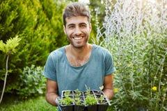 Nära för u stående utomhus av den härliga glade latinamerikanska mannen i blå skjorta som ler med tänder som rymmer krukan med Fotografering för Bildbyråer
