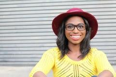 Nära framsida av den afrikanska kvinnlign med exponeringsglas och den röda hatten fotografering för bildbyråer