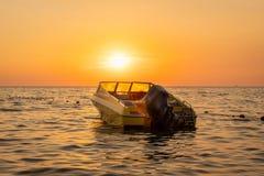 Nära härlig havssikt av apelsinen och gulingsolnedgången med en förtöjd motorbåt mot horisonten arkivbilder