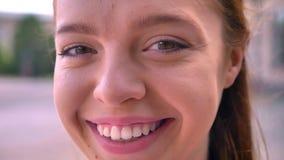 Nära längd i fot räknat av den unga ljust rödbrun kvinnan som ler på kameran, stående av den lyckliga och gladlynta kvinnlign, ga arkivfilmer