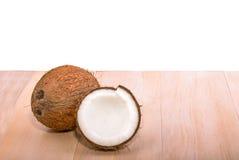 Nära ny, organisk brun kokosnöt på en ljus trätabell som isoleras på en vit bakgrund En smaklig hel kokosnöt exotisk frukt arkivbilder