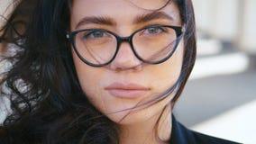 Nära porträtt av en ung, vacker affärskvinna i glasögon utomhus nära modern kontorsbyggnad Flickor som tittar på arkivfilmer