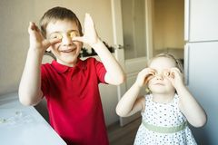 Nära rolig syskongrupp deras ögon med godisen som exponeringsglas arkivfoton