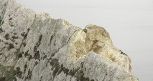Nära sikt av överkanten av en klippa i havet lager videofilmer