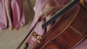 Nära sikt av den kvinnliga violoncellisten som spelar på raderna med fiolstråke lager videofilmer