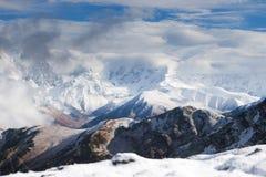 Nära sikt av den snöig bergkanten som döljas i moln georgia Fotografering för Bildbyråer